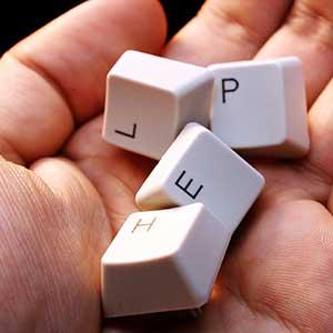 """Hånd holder tatstaturknapper, der til sammen danner det engelske ord """"help"""", der på dansk betyder """"hjælp"""""""