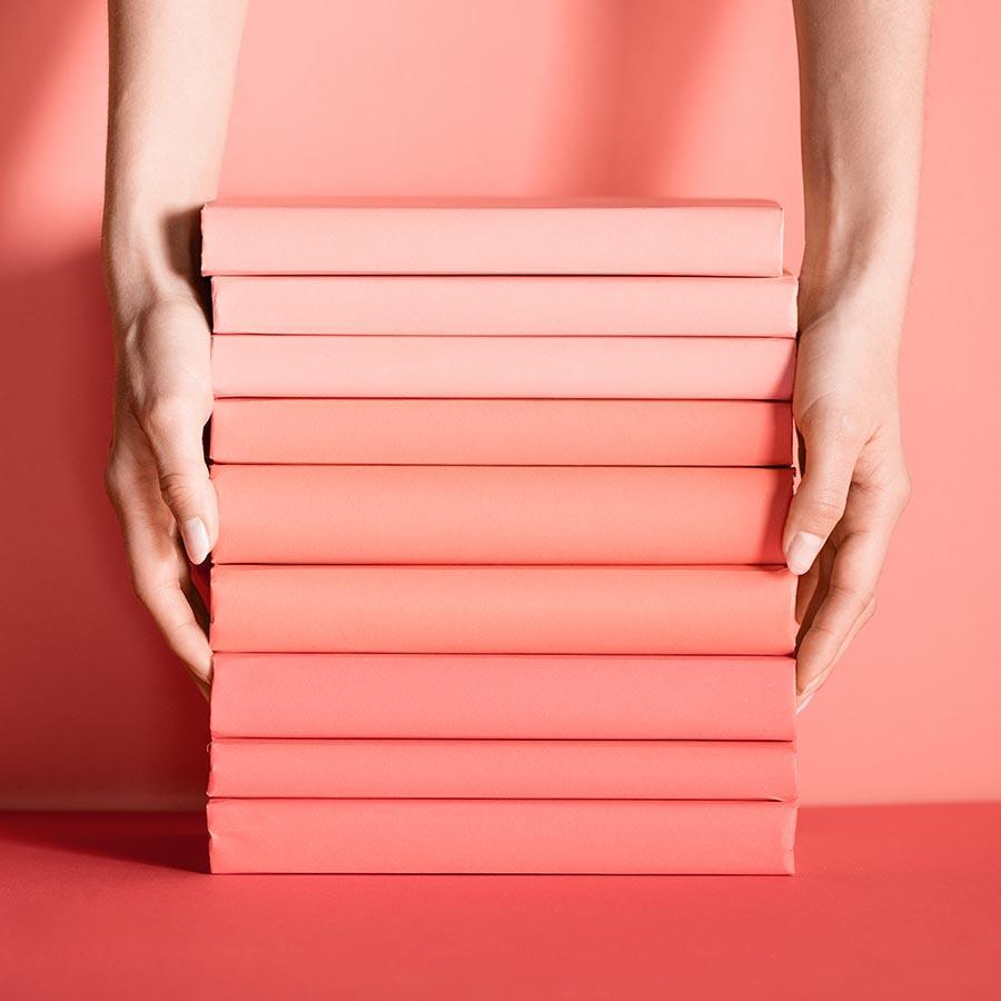 Foto af en stabel bøger i rødlige nuancer, der bliver holdt af to hænder