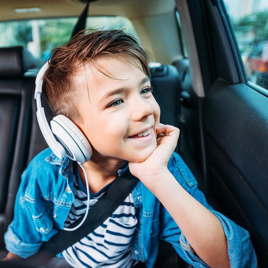 Foto af dreng med høretelefoner på bagsædet af en bil