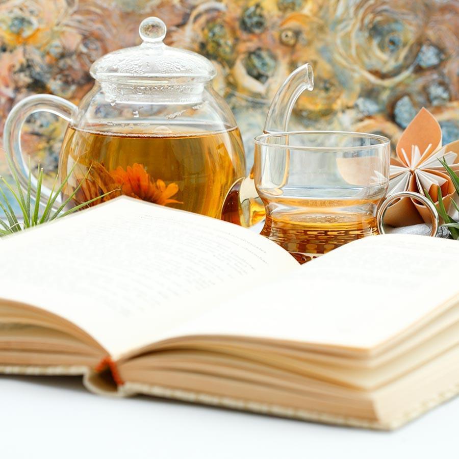 Foto af en åben bog og en kop te