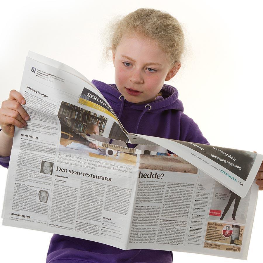 Foto af barn der læser avis