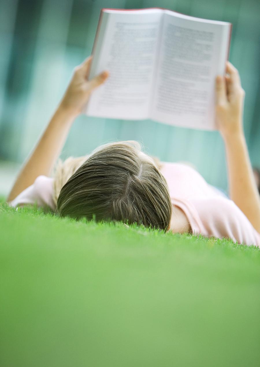 Kvinde ligger og læser