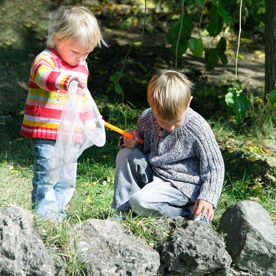 Foto af to børn der udforsker naturen