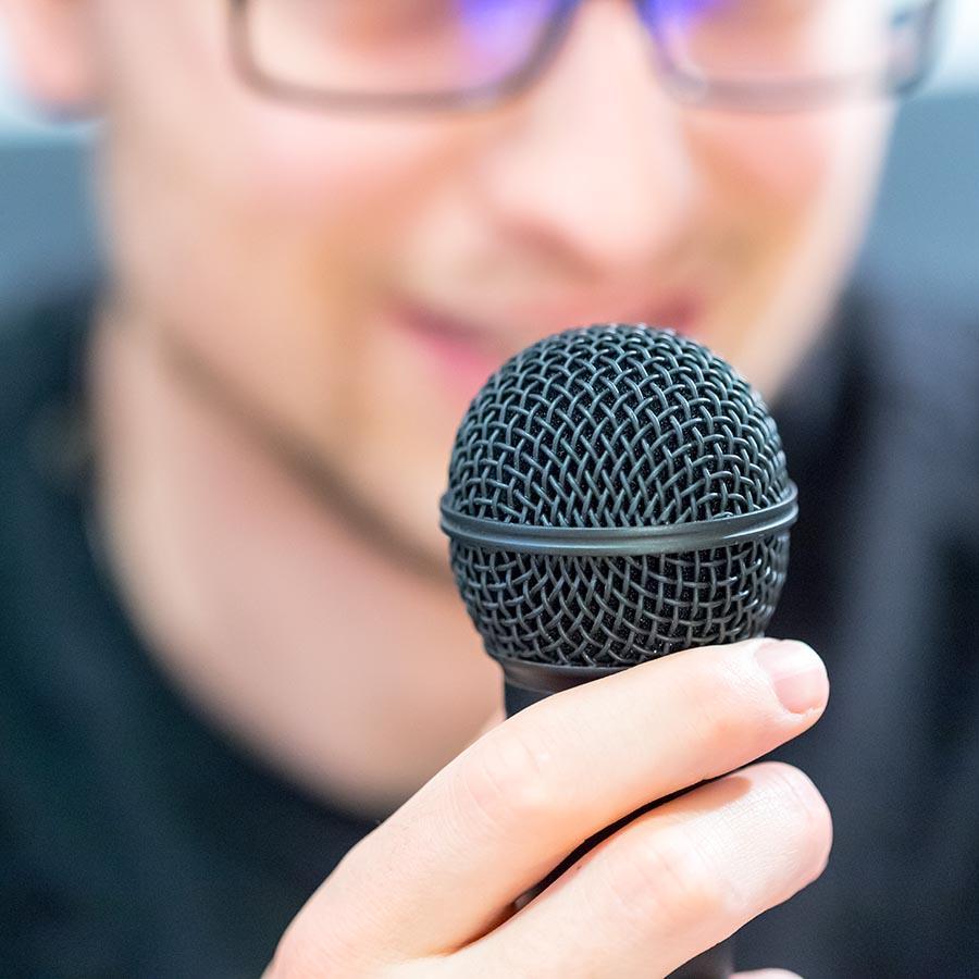 Foto af mand der taler ind i en mikrofon