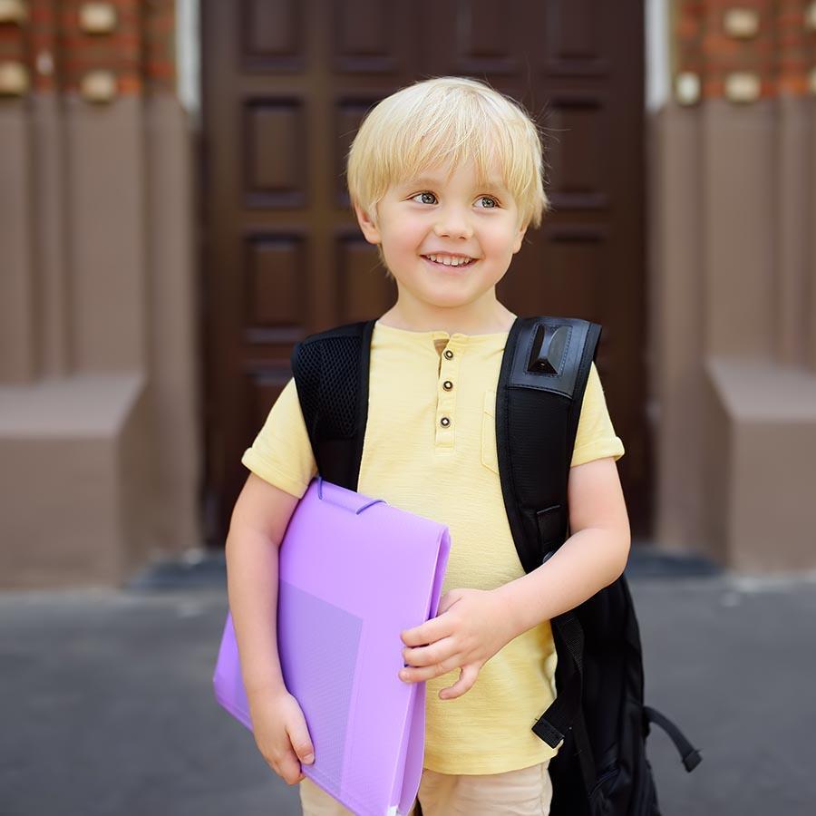 Foto af skoleklar dreng foran skole