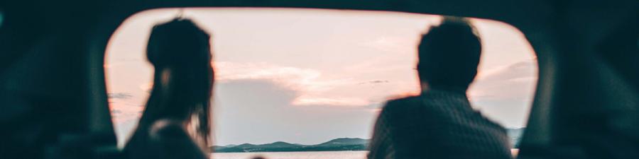 To unge mennesker sidder og kigger ud på solnedgangen